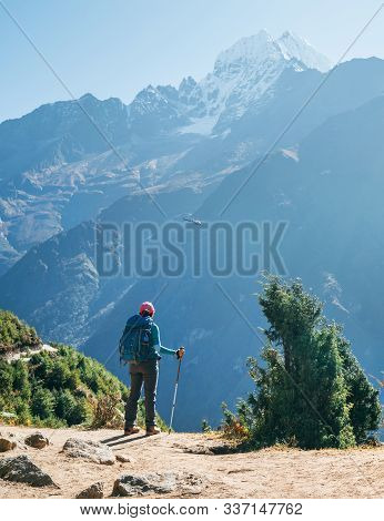 Young Hiker Backpacker Woman Using Trekking Poles Enjoying The Thamserku 6608m Mountain With Flying