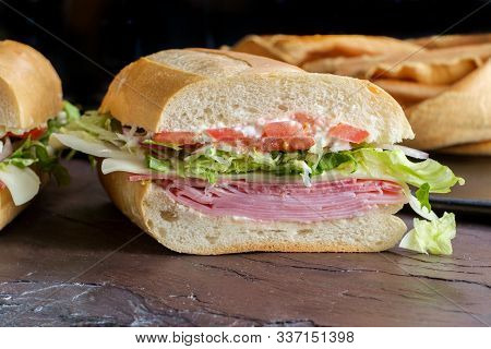 Italian Sub Sandwich With Ham And Genoa Salami On Slate Kitchen Table