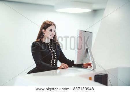 Sideview On A Caucasian Businesswoman Using A Reception Computer To Make A Meeting Room Reservation;