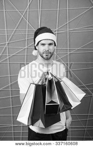 Xmas Sale Concept. Macho Shopper In Red Hat Hold Paperbags. Christmas, New Year Gift, Present. Winte