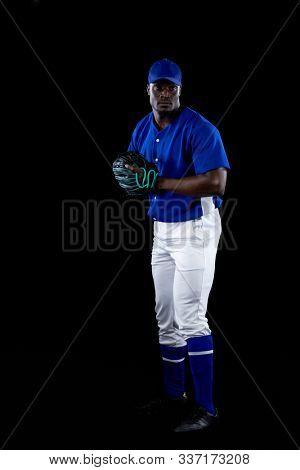 Front view of an African American male baseball player, a pitcher or fielder, wearing a team uniform, baseball cap and a mitt