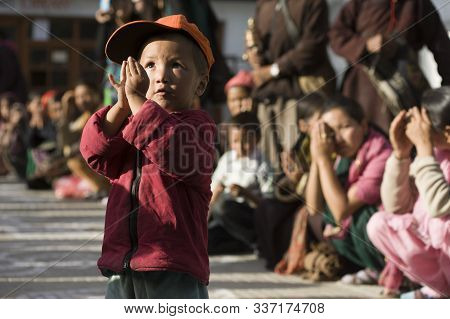 Leh, Jammu And Kashmir, India - July 27, 2016: Cute Little Boy Praying During Buddhist Ceremony In L