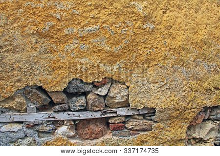 Background Texture Of A Typical Building Wall Of Yellow Stucco And Brick In Athens, Greece With Copy