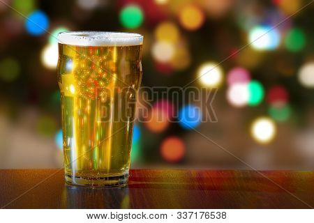 Pint Of Beer With Christmas Tress Lights On The Background