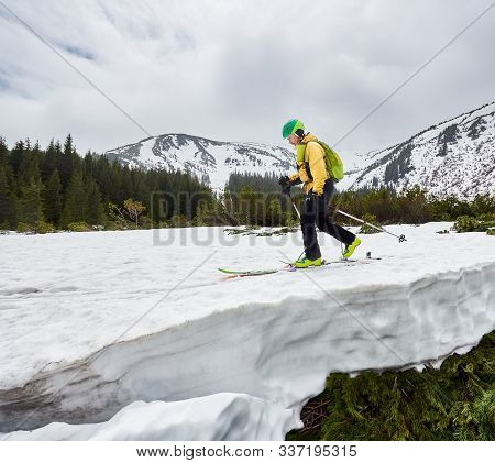 Snow-covered Mountain And Off-piste Skier. Side View Of Cross Country Skier Man In Green Helmet Walk