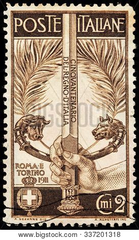 Luga, Russia - October 25, 2019: A Stamp Printed By Italy Shows Sword Wielded By A Hand, The Hilt Sy