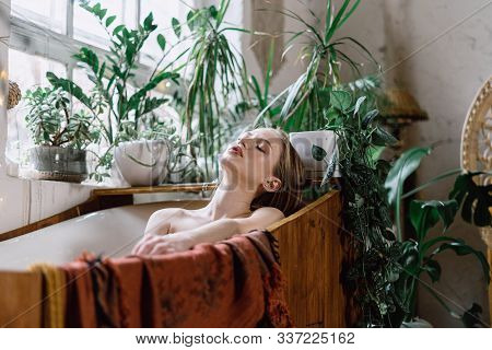 Young Adult Woman Taking Pleasant Bath, Relaxing At Spa, Enjoying Skincare And Bodycare Procedure In