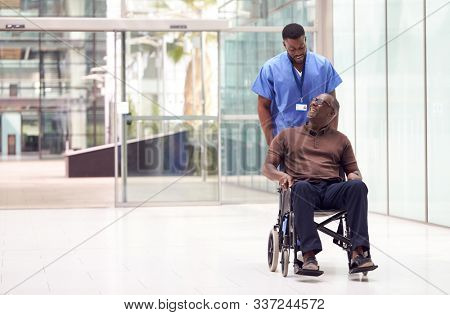Male Nurse Wearing Scrubs Wheeling Patient In Wheelchair Through Lobby Of Modern Hospital Building