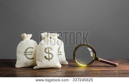 Three Bags Of Money And A Magnifying Glass. Search For Investments And Financing For Projects. Savin