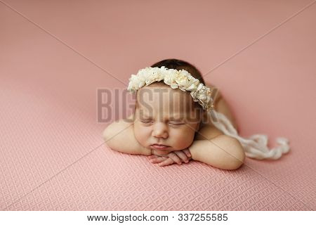 Portrait Of A Beautiful Sleeping Newborn Baby Girl On A Pink Background With A Floral Headband. Pose