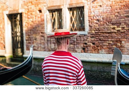 Gondolier In Gondolier Hat On Canal Street In Venice, Italy.