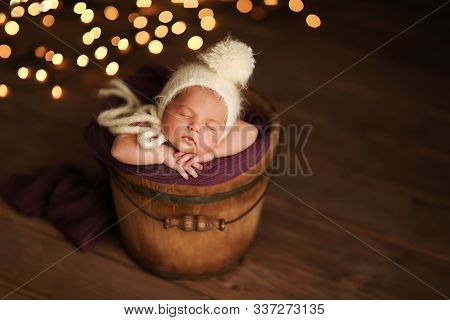 A Cute Newborn Girl Sleeps In A Bucket On A Vintage Wooden Background, And In The Background Is Brig