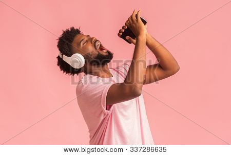 Emotional African American Man Dancing, Singing His Favorite Song On Smartphone With Closed Eyes, Us