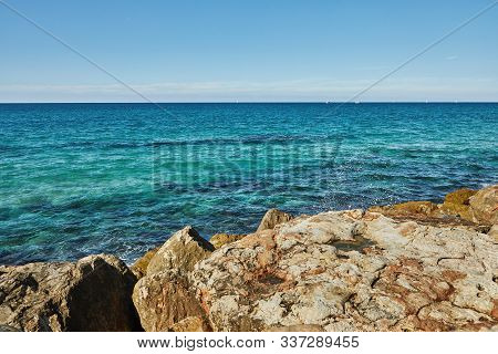 Mediterranean Sea With Waves Crashing On Stones, Yachts And Boats On The Garrison On A Bright Sunny