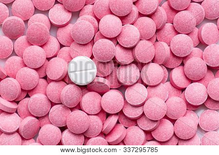 Pile Of Pink Pills And Around A White One. Medication, Self-treatment Or Placebo Concept: One Tablet