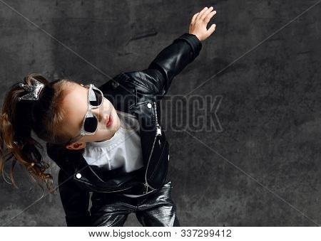 Frolic Kid Girl With Silver Crown Hairpin And In Leather Jacket And Sunglasses Is Having Fun Dancing