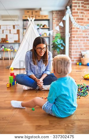 Young caucasian child playing at playschool with teacher. Mother and son at playroom bulding a tower with toy blocks