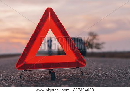 Warning Triangle Sign On The Road, Woman In Blur Background Calling For Roadside Assistance By The B