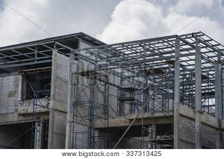 Building And Construction Site In Progress. Building Construction Site Against Cloudy Sky. Metal Con
