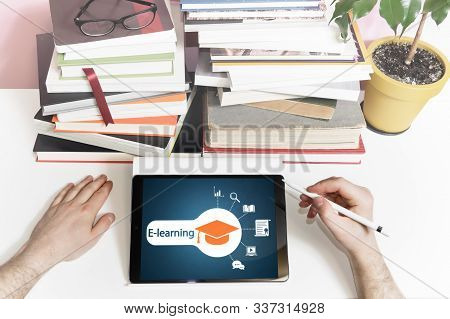 Tablet, Pen, Book, Glass, Houseplant And Man Hands On The Desk. Tablet With Different Education Icon