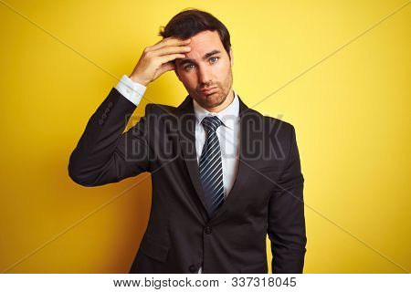 Young handsome businessman wearing suit and tie standing over isolated yellow background worried and stressed about a problem with hand on forehead, nervous and anxious for crisis