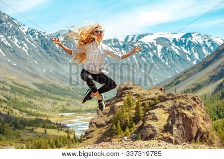 Beautiful Happy Girl Jumps In Yoga Pose Against Mountains Valley