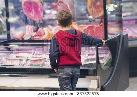 Boy At The Counter Of A Butcher's Shop. People