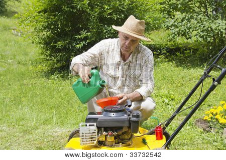 Mid age man adding oil to lawnmover