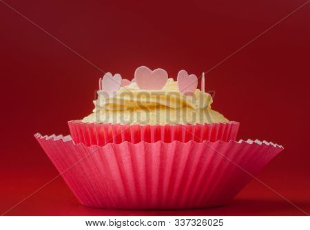 Vanilla Cupcake With Eatable Hearts On Vanilla Icing, Red Background