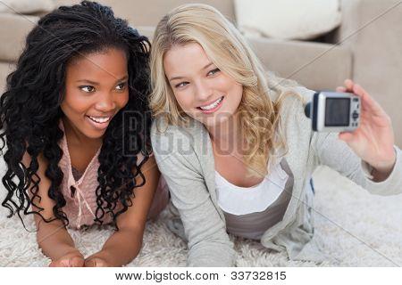 zwei Freunde, die mit einer digitalen Kamera auf dem Boden liegend sind für ein Foto posieren.