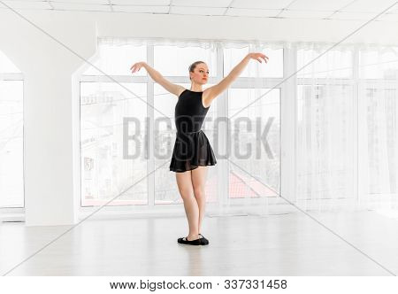 Beautiful ballerina in black leotard practising ballet moves in white bright room