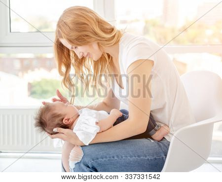 Young mother hugging cute baby at home