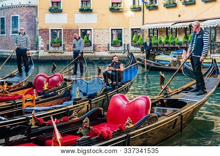 Group Of Gondolas Moored In Front Of The Popular Cavalletto Hotel, Orseolo Basin In Downtown Of Veni