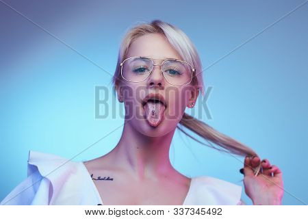 Closeup Portrait Of A Cocky Blonde Girl Wearing Glasses Poses With Tongue Sticking Out Looking At Th