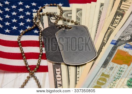Against the background of the American flag and dollar bills lie army identification medallions. Concept: military pension, salary in the army, insurance for the military, mercenaries and contractors. 7 poster