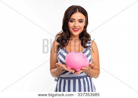 European Attractive Brunette In Dress Holds A Piggy Bank In Her Hands On A White Studio Background.