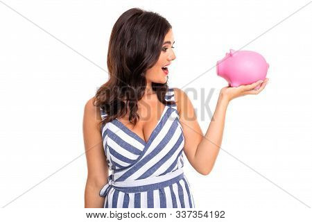 European Attractive Girl In Dress Holds A Piggy Bank In Hands On A White Studio Wall.
