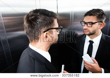 High Angle View Of Businessman In Suit Looking At Mirror In Elevator