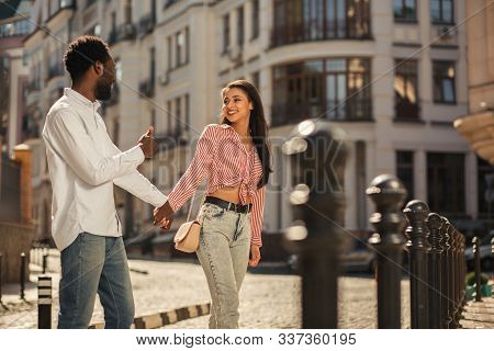 Mirthful Young Couple Walking In The Street And Smiling