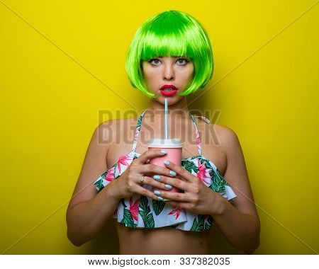 Beautiful Young Woman In A Bright Green Wig Under A Quack And A Swimsuit Posing On A Yellow Backgrou