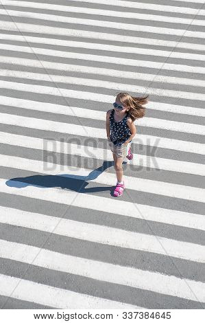 In The Summer On The Street At The Pedestrian Crossing Kid Girl In Fashion Clothes Cross The Road. Z