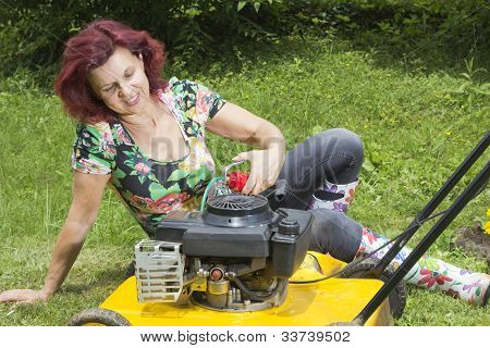 Smilling women oiling lawn mover