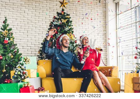 Romantic Sweet Couple In Santa Hats Having Fun Decorating Christmas Tree And Smiling While Celebrati
