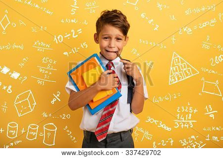 Child Cries Because He Has A Lot Of School Homework. Emotional Expression. Yellow Background