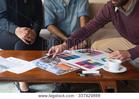 Interior Designer Presenting Drawings And Swatches While Discussing Renovation Project With Clients.