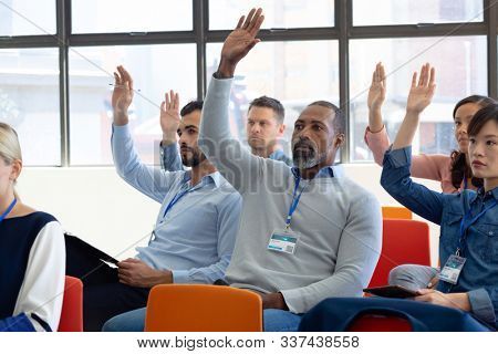 Front view of a diverse group of business creatives sitting in the audience at a business conference, all raising their hands to ask questions