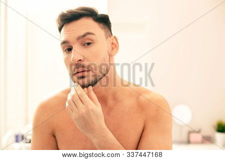 Curious Man Frowning And Touching His Unshaved Beard
