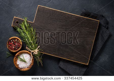 Food Cooking Background On Black. Black Wooden Cutting Board, Herbs And Spices On Black Stone Table.