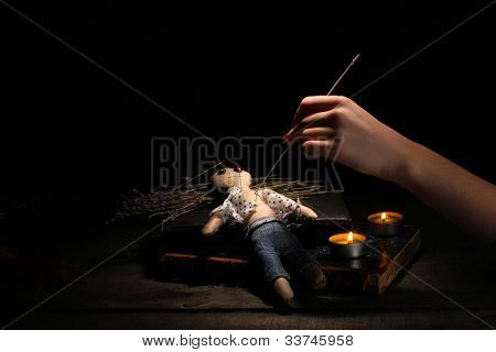 Voodoo doll boy pierced by a needle on a wooden table in the candlelight