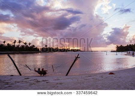 North Male Atoll, Maldives - November 23, 2019: A Happy Adult Couple Relaxes In A Hammock Over The W